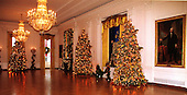 This photo shows three of the six trees in The East Room, the largest room in the White House in Washington, D.C. on December 6, 1999.  The traditional White House creche is at the right center of the photo..Credit: Ron Sachs / CNP