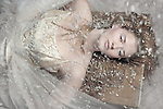 A beautiful young blond woman in a beaded white dress looking like a snow queen while laying down with snow falling on her.