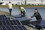 Foto: VidiPhoto<br /> <br /> BEMMEL &ndash; Personeel van Tenten Solar uit Lichtenvoorde legt woensdag een enorme glazen puzzel in een gietwaterbassin in het kassengebied Nex Garden (voormalig Bergerden) bij Bemmel, gemeente Lingewaard. De bouw van een enorm drijvend zonnepark met 6000 zonnepanelen in de 3 ha. grote plas, een van de grootste van ons land, moet eind deze maand gereed zijn. Het particuliere initiatief van &ldquo;Lingewaard Energie&rdquo;, met 70 aandeelhouders, wordt onder andere gesubsidieerd door de provincie Gelderland. De stroom die wordt opgewekt is goed voor het verbruik van 600 huishoudens. De collectoren liggen op verankerde drijvers en bewegen mee met de waterstand. Het gietbassing wordt gevuld via regenwater uit sloten en in de kassen gebruikt als sproeiwater. De panelen houden het zonlicht tegen waardoor er minder water verdampt en er van minder algengroei sprake is. Drijvende zonneparken zijn er op dit moment nog maar weinig. Lingewaard Energie wil er nog twee in de regio.