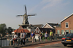 People crossing bridge over the Spaarne River, with the De Adriaan Windmill Museum Haarlem, Holland, Netherlands.