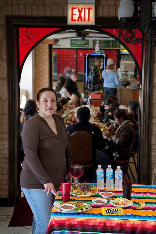 Lourdes Alvarez, a restaurant owner and chef with her typical day's worth of food in her family's Mexican restaurant, Los Dos Laredos in Chicago. (From the book What I Eat: Around the World in 80 Diets.) The caloric value of her typical day's worth of food on a day in the month of September was 3,200 kcals. She is is 39 years of age; 5 feet, 2.5 inches tall; and 190 pounds.   She grew up in an apartment above Los Dos Laredos, where she still helps out two days a week. Other days she spends long hours at her own restaurant in Alsip, Illinois. At right: Lourdes takes a phone order, while her daughter, Alejandra, checks her mobile phone after school. MODEL RELEASED.