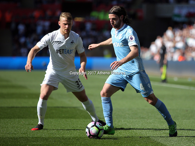 SWANSEA, WALES - APRIL 22: Joe Allen of Stoke City (R) is closely followed by Stephen Kingsley of Swansea City  during the Premier League match between Swansea City and Stoke City at The Liberty Stadium on April 22, 2017 in Swansea, Wales. (Photo by Athena Pictures/Getty Images)