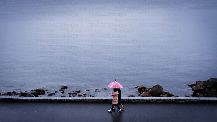 Two women walking under pink striped umbrella against dark ocean on rainy day.