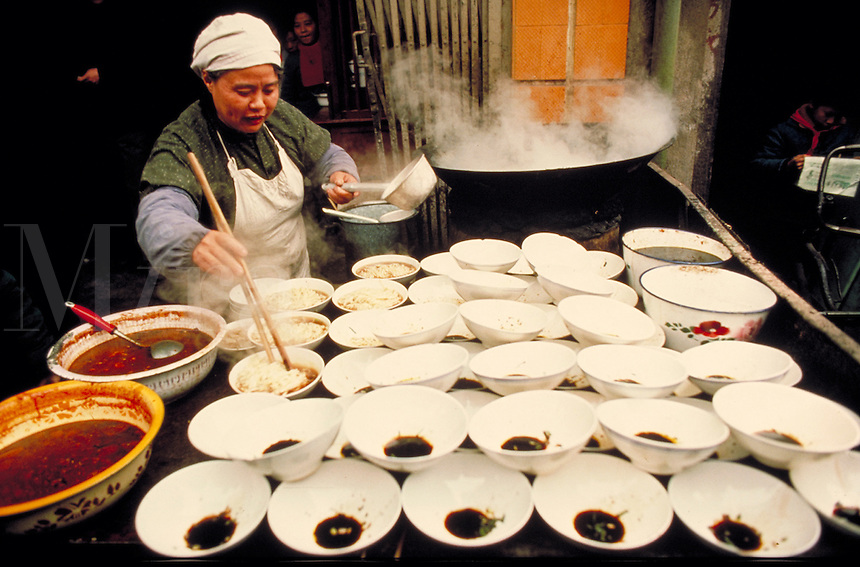 A Chinese woman prepares food and serves it in rows of bowls at an out door food stall. Cooking. Skills. Professions. People. Market. Chinese cook. China.