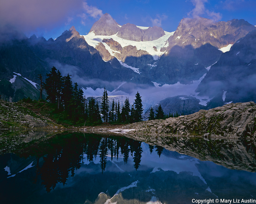North Cascades National Park, WA<br /> Afternoon sun on Mount Shuksan breaks through clearing fog with a mirror reflection in Lake Ann