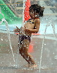 Athena Miliopulos, age 3 of Lindenhurst, is tickled by the small fountains of the Water Playground in Tanner Park in Copiague on Friday August 31, 2007. For her this was a perk of a day at the office with parents who operate an Ice Cream truck can take their children to work. Photo by Jim Peppler.