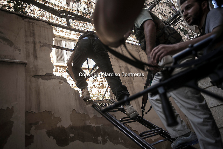 Rebel fighters belonging to the Liwa Al Tawhid move to the frontline through a house wall as they avoid the snipers army at the Saif Al Dawla battlefield in southwest of Aleppo City.