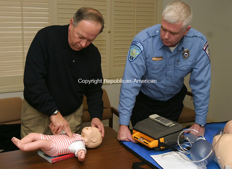 SOUTHBURY, CT 01/27/08- 012708BZ03- Lewis Capuano, of Southbury, left, practices CPR on an infant doll as EMS instructor Gregory Skelly looks on at the Southbury Ambulance Association headquarters Sunday.<br /> Jamison C. Bazinet Republican-American