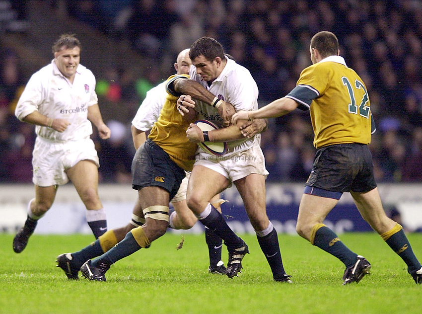 Photo. Richard Lane. .England vs Australia - Twickenham.18.11.00.Martin Johnson being tackled by Jim Williams, with Stirling Mortlock on hand to help him with the job.