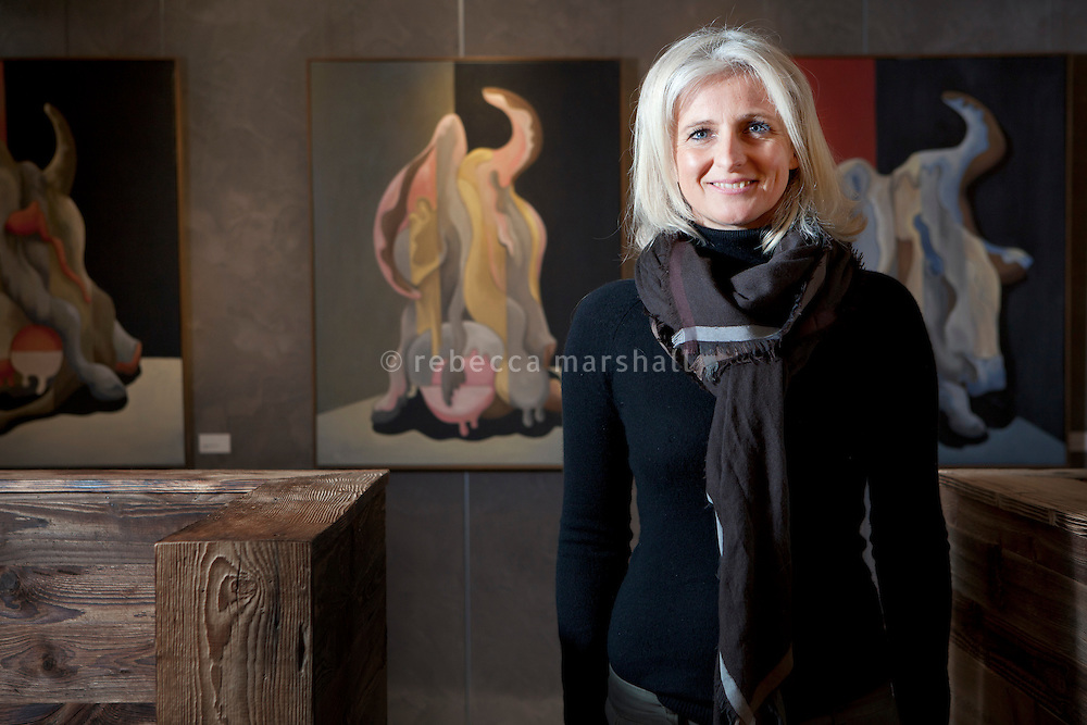 Artist Catherine Kiecken-Playe poses for the photographer in front of an exhibition of her work at the Hotel Au Coeur du Village, La Clusaz, France, 15 February 2012. The series of 3 paintings shown is entitled Variations 1, 2 & 3 (right to left).