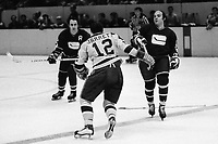 Seals Gary Jarrett after Canucks Jocelyn Guevremont and Ron Ward or Bobby Laionde.<br />(1971 phfoto/Ron Riesterer)