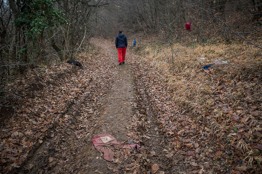 Dimitrovgrad, Serbia-- December 16, 2015--Aleksandar Nackov, who comes from a border village (in Serbia) called Gradina, walks on a dirt path littered with discarded clothes and documents used by immigrants crossing from Bulgaria to Serbia that runs near his family's farmhouse. Nachov works for Save the Children in nearby Dimitrovgrad.