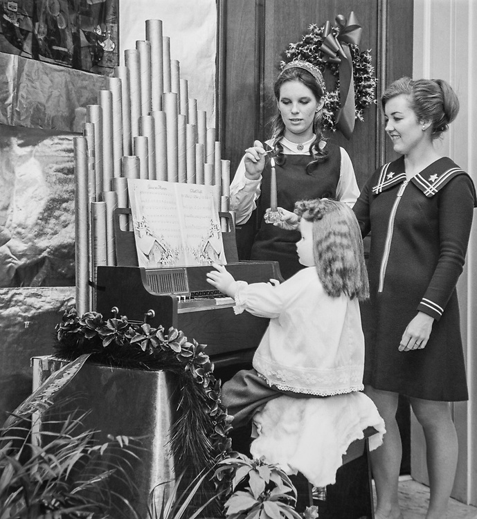 Staff members lighting up candle near decorated piano and doll decoration at Congressman's office during Christmas. (Photo by CQ Roll Call via Getty Images)