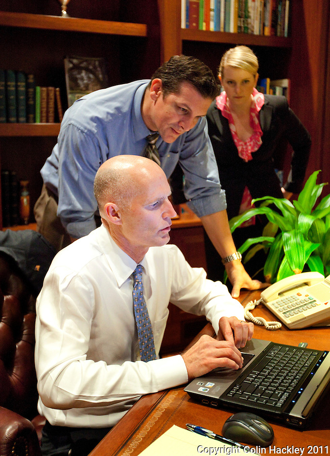 TALLAHASSEE, FLA. 1/20/11-SCOTT12011HACKLEY07-Gov. Rick Scott, left, responds to questions on Twitter as Brian Burgess and Amy Graham, both of his communications office, look over his shoulder during a Twitter town hall meeting Thursday at the Governor's Mansion in Tallahassee..COLIN HACKLEY PHOTO