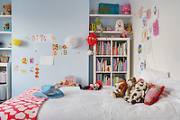 This girl's bedroom is furnished with colourful books and an assortment of soft toys on the bed
