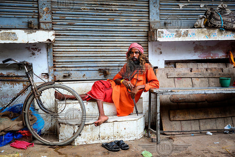 A sadhu rests on the steps of a shuttered shop.