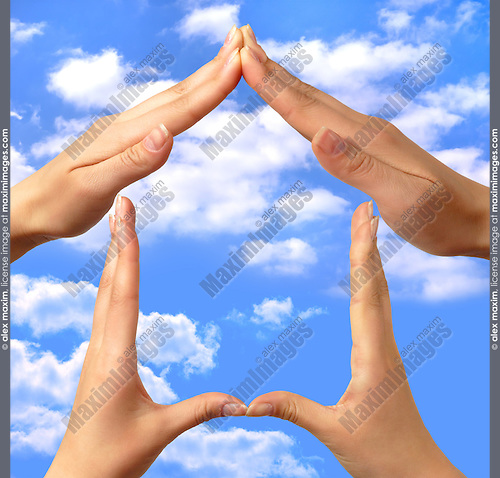 Female hands showing home sign family house concept sky background
