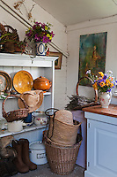 The utility room is used as a place to store boots and baskets and also for flower arranging
