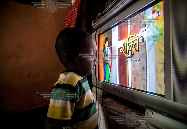 Two year old Bakir Rashid, who suffers from congenital cataracts, stares at the television at his hom, a week before undergoing an operation to remove the cataracts.