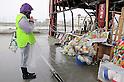"""Minamisanriku, Miyagi, Japan - A volunteer prays in front of floral tribute at the building of disaster measures in Minamisanriku, one year after the tsunami. The Latin group of volunteers """"Todos con Japon"""" visits Miyagi area during this Golden Week."""