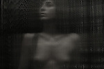 A young woman standing naked behind a corrugated sheet of glass