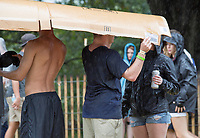 With few options for shelter from the pouring rain, Music Midtown festival-goers make do with whatever they can find to wait out the storm.
