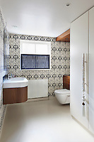 A bathroom with a resin floor and decorated with blue and white patterend wallpaper
