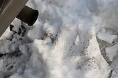 A diesel van's exhaust impurities show up on the snow.