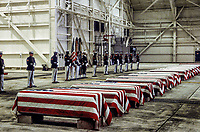 Dover, Delawre, USA, October 29, 1983<br /> At precisely 7 A.M., a Marine honor guard and a color guard in ceremonial dress uniforms marched into a huge hangar at the Dover Air Force Base and stood facing 16 coffins. Behind them, suspended from the beams of the hangar, was a 38-foot American flag.<br /> The ceremony was the first on American soil honoring servicemen killed in the bombing in Beirut and the invasion of Grenada. Credit: Mark Reinstein/MediaPunch