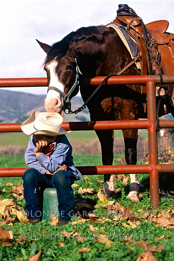 Horse nibbling on young cowboys hat, San Luis Obispo, California.