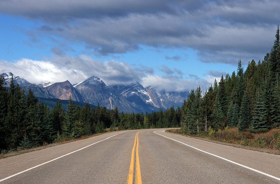 A road in Alberta Canada curves alongside the Canadian Rockies.