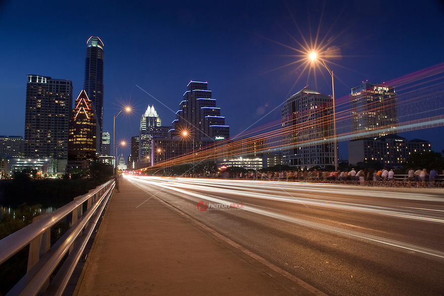 Car lights leave streak trails as they drive down Congress Avenue Bridge filled with bat watchers in downtown Austin, Texas, USA