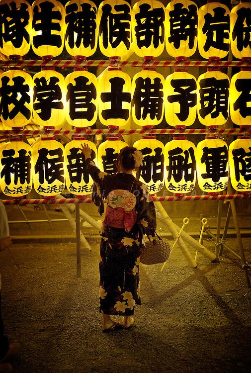 Tokyo - 16th of July 2009 - A young girl wearing a traditional yukata touching a lantern at Yasukuni Shrine during O-bon matsuri.