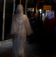 Streetscene, Meknes, Morocco pictured on December 26, 2009. A veiled woman, in a white Djellaba, walks towards a light through the dark streets.  Meknes, one of Morocco's Imperial cities, was redeveloped under Sultan Ismail Moulay (1634-1727). It is a fortified city built from pise, or clay and straw, and was designed to be the political capital of Morocco, as opposed to Fez, the religious capital. Picture by Manuel Cohen