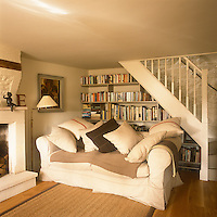 A country sitting room decorated in neutral tones with a staircase in one corner. An upholstered sofa piled with cushions stands in front of shelving set in the recess under the stairs.