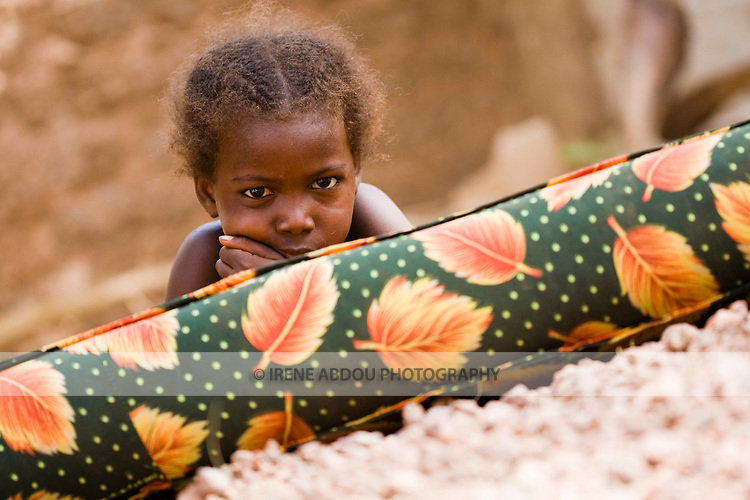 A Fulani child in Ouagadougou, Burkina Faso, rests outdoors on a mattress in the summer sun.