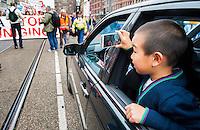 Nederland, Amsterdam, 21 sept 2013<br /> Demonstratie tegen bezuinigingen door het kabinet Rutte2.  Een chinees jochie in een mercedes maakt een filmpje met de iphone van zijn moeder als de auto moet wachten op de demonstratie.<br /> Demonstration against cuts by the government. A chinese boy in a Mercedes makes a movie with his mothers iPhone   while  waiting for the demonstration.<br /> Foto(c): Michiel Wijnbergh
