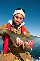 Man holding the Arctic char he caught spin casting in the Arctic ocean near Nunavut, Canada.