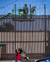 "MEXICALI,  MEXICO - November 26. A street vendor gestures while US Army soldiers are seen from the mexican side fortifying US-Mexico border fence with barbed wire on November 26, 2018 in Mexicali, Mexico.<br /> The U.S. government said it was starting work to ""harden"" the border crossing  Mexico, to prepare for the arrival of a migrant caravan leapfrogging its way across western Mexico. For the Trump administration and those who support the president's hard-line stance on illegal immigration, the chaos illustrated what they long have feared. For others, the images of the Border Patrol using tear gas on a group of migrants that included children were deeply disturbing (Photo by Luis Boza/VIEWpress)"