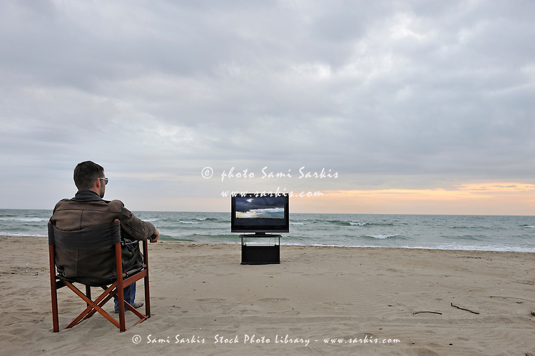 Man watching TV on beach at sunset