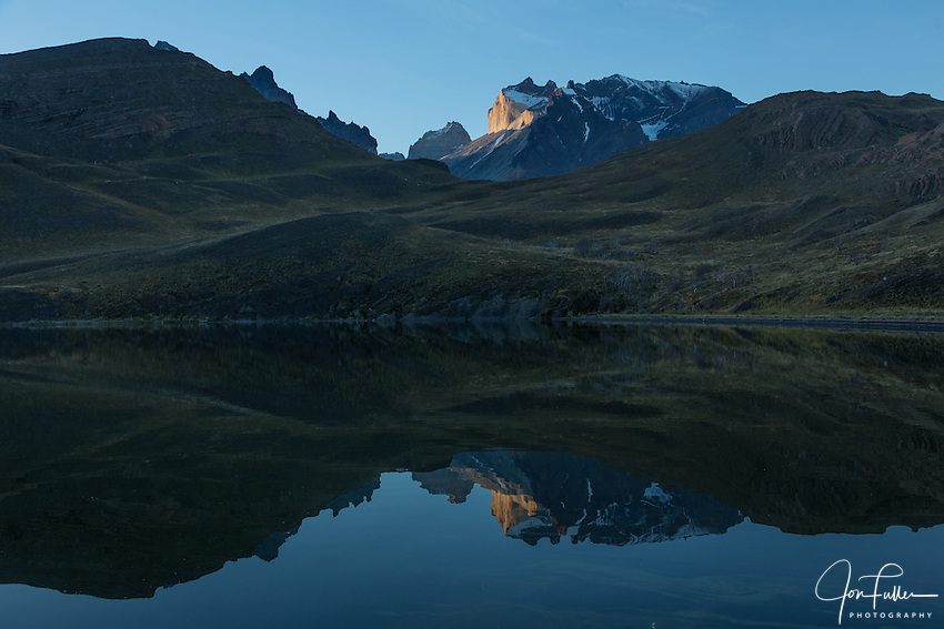 Sunset light on the face of Monte Almirante Nieto reflected in Laguna Melliza.  Just to the left is the top of Torre Sur, or the South Tower, of the Torres del Paine.  Torres del Paine National Park in Patagonia, Chile.  A UNESCO World Biosphere Reserve