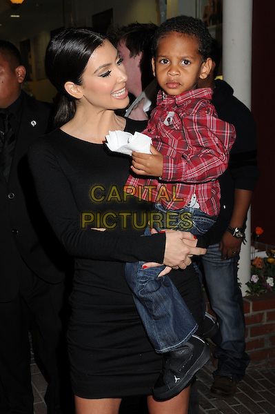 KIM KARDASHIAN & KIYAN ANTHONY.Famous Cupcakes Beverly Hills Grand Opening Hosted by The Kardashians held at the Famous Cupcakes Store, Beverly Hills, California, USA..October 7th, 2009.full length dress black cut out side hair up  long sleeved sleeves profile carrying child kid jeans denim red plaid shirt.CAP/ADM/BP.©Byron Purvis/AdMedia/Capital Pictures.