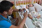 Jeff Florendo watches videos on his phone as he sits by the bedside of his six-month old son Charles in the Mary Johnston Hospital in Manila, Philippines. The boy was suffering from diarrhea. <br /> <br /> The hospital is supported by United Methodist Women.