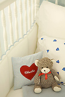 Detail of a teddy bear and a personalized cushion in a little boy's cot