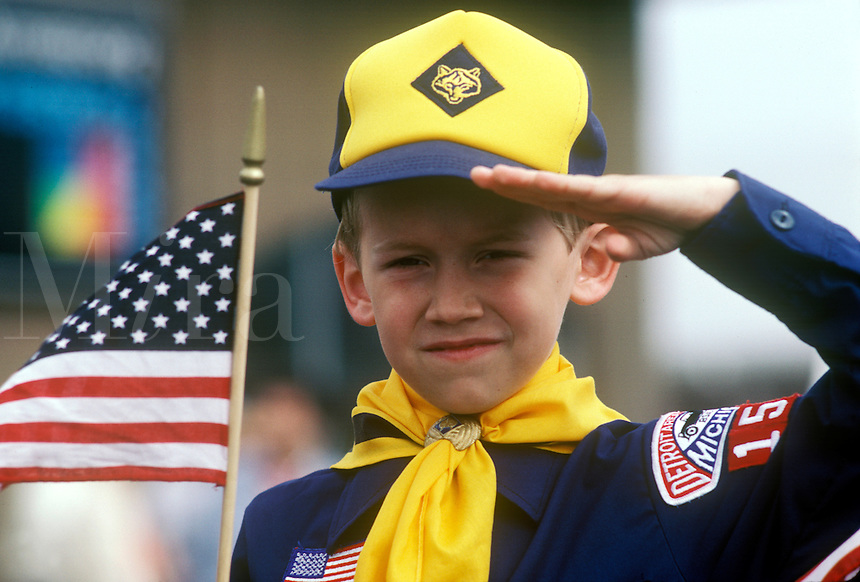 American Cub Scout  salutes as he holds an American flag