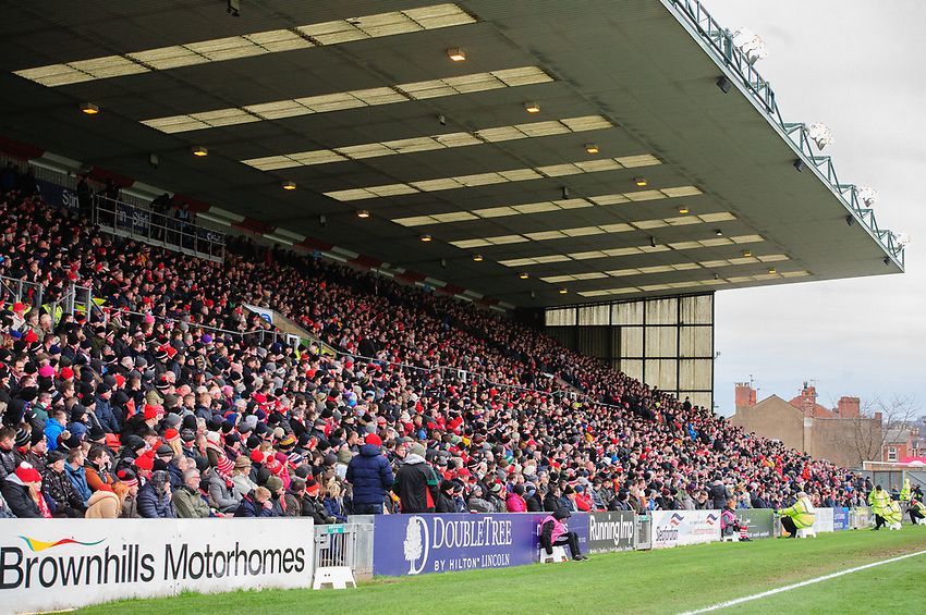 Lincoln City fans watch their team in action<br /> <br /> Photographer Chris Vaughan/CameraSport<br /> <br /> The EFL Sky Bet League Two - Lincoln City v Grimsby Town - Saturday 19 January 2019 - Sincil Bank - Lincoln<br /> <br /> World Copyright © 2019 CameraSport. All rights reserved. 43 Linden Ave. Countesthorpe. Leicester. England. LE8 5PG - Tel: +44 (0) 116 277 4147 - admin@camerasport.com - www.camerasport.com