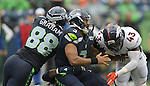 Seattle Seahawks quarterback Russell Wilson is sacked by Denver Broncos linebacker Von Miller and safety T.J. Ward (43) during the first quarter at CenturyLink Field on August 14, 2015 in Seattle Washington.  The Broncos beat the Seahawks 22-20.  © 2015. Jim Bryant Photo. All Rights Reserved.