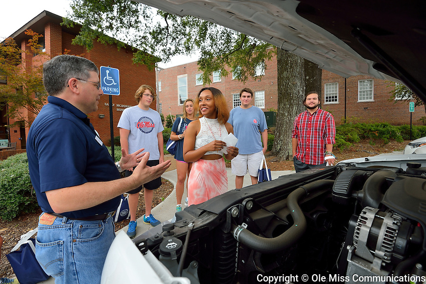 John Samonds, associate dean of the Sally McDonnell Barksdale Honors College, goes over car-care basics with freshmen as part of the college's Welcome Week. Photo by Robert Jordan/Ole Miss Communications