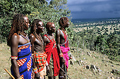 Four Siria Maasai moran warriors standing on a hill, looking out over the countryside