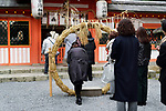 Woman stepping through a large straw ring at a Japanese Shinto shrine for Chinowa Kuguri rite, summer purification ritual, at Uji-jinja, Uji Shrine in Uji, Kyoto Prefecture, Japan 2017
